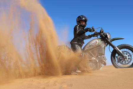 Scrambler sobre duna atascada arena en alto